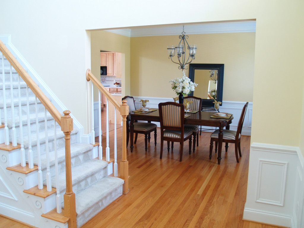 A well staged dining room viewed from the foyer with the staircase in the foreground